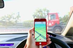Pokemon GÅR: Chaufförlekpokemon går på bilen under att köra Royaltyfria Bilder