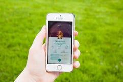 Pokemon går på iPhonen, skärmen som visar Charmander pokemon Arkivbilder