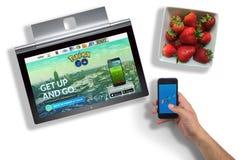 Pokemon gaat website op laptop het scherm en app op hand - gehouden telefoon stock afbeeldingen