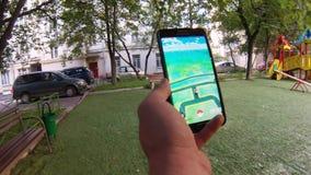 Pokemon gehen APP, die von einem Mann an seinem Handy beim Gehen auf Garten gespielt wird stock video