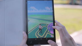 Pokemon Go app being played by a man on his tablet. stock footage