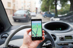 Pokemon Go App. VELIKA GORICA, CROATIA- JULY 15, 2016 : A gamer using a smartphone to play Pokemon Go while driving a car. Pokemon Go is a free-to-play augmented Stock Images