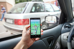 Pokemon Go App. VELIKA GORICA, CROATIA- JULY 15, 2016 : A gamer using a smartphone to play Pokemon Go while driving a car. Pokemon Go is a free-to-play augmented Royalty Free Stock Image