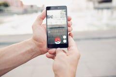 Pokemon Go che gioca il gioco dello smartphone addicted Immagine Stock Libera da Diritti
