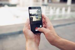 Pokemon Go che gioca il gioco dello smartphone addicted Fotografia Stock Libera da Diritti
