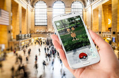 Pokemon Go. The new augmented reality game that lets you walk in the real world to catch the monsters. An user plays , a free-to-play game developed by Niantic Royalty Free Stock Image