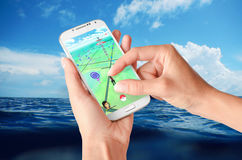 Pokemon Go on hand held white smartphone on the sea. Pokemon Go app on hand held smartphone on blue sea background Stock Image