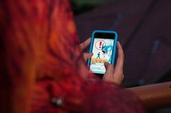 Pokemon Go. Hokkaido, Japan - 25 July 2016. Muslim Female Playing Pokemon Go with an iPhone during sunset Royalty Free Stock Image