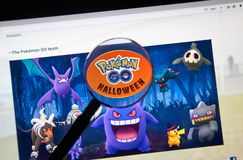 Pokemon Go Home Halloween page under magnifying glass Stock Photos