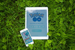 Pokemon Go on iPhone and iPad. TRIM, IRELAND - JULY 18, 2016: Pokemon Go app on iPad Air and iPhone 5s. Pokémon Go is a popular location-based augmented reality Stock Images