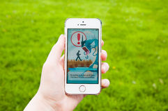 Pokemon Go loading screen on iPhone. TRIM, IRELAND - JULY 18, 2016: Apple iPhone 5s held in one hand showing loading screen of the Pokemon Go app. Pokémon Go is Royalty Free Stock Photo