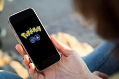 Woman sitting in the street holding her smartphone with pokemon. Pokemon Go logo on the phone. Pokemon Go is a location-based augmented reality mobile game Royalty Free Stock Photography