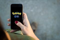 Woman walking smartphone  pokemon go. Pokemon Go logo on the phone. Pokemon Go is a location-based augmented reality mobile game Stock Photo