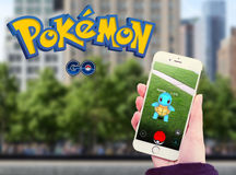 Pokemon Go in mobile With Logo. Roseville, CA - July 10: An Android user plays Pokemon Go, a free-to-play augmented reality mobile game developed by Niantic for
