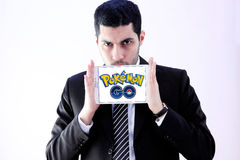 Pokemon go. Most famous smartphone game pokemon go logo on white tablet holded by arab muslim businessman.this game is travel between the real world and the Stock Photo