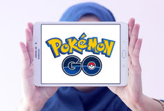 Pokemon go. Most famous smartphone game pokemon go logo on white tablet holded by arab muslim woman.this game is travel between the real world and the virtual Royalty Free Stock Images