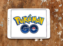 Pokemon go. Most famous smartphone game pokemon go logo on white tablet on wooden background.this game is travel between the real world and the virtual world of Stock Image