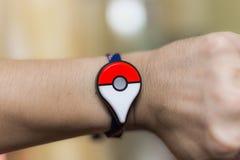 Pokemon Go Plus. Bangkok, Thailand - October 29: A Pokemon Go player wears the new Pokemon Go Plus on their wrist. Pokemon Go is a free-to-play augmented reality stock photos