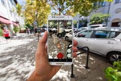 Pokemon GO in an Urban Setting. SANTA CRUZ, CALIFORNIA - AUGUST 7, 2016: The hit augmented reality smartphone app Pokemon GO shows a Pokemon encounter in the Royalty Free Stock Photo