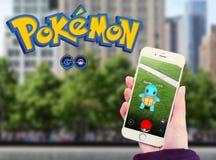 Pokemon går i mobil med logo Royaltyfri Bild