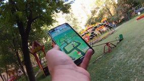 Pokemon va app que es jugado por un hombre en su teléfono móvil mientras que camina en jardín almacen de video