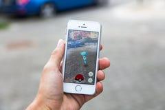 Pokemon va juego en la pantalla del iPhone Foto de archivo libre de regalías