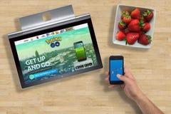Pokemon va sito Web sullo schermo del computer portatile ed app sul telefono tenuto in mano Fotografie Stock Libere da Diritti