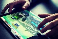 Pokemon va sito Web sullo schermo nero della compressa con le mani maschii Fotografie Stock Libere da Diritti