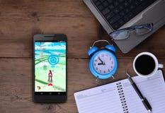 Pokemon vont APP dans le mobile sur la table de travail Image stock