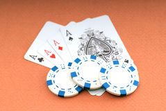 Poker. Cards, four of a kind of aces and chips on orange background Royalty Free Stock Image
