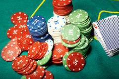 Poker. Batch of cards and poker chips on a green table in casino Royalty Free Stock Photos