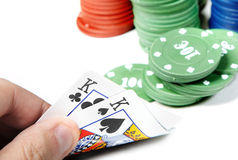 Poker. Pair of kings in human hand and poker chips on a white background Royalty Free Stock Images