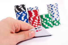 Poker. Chips stack and playing cards in hand Stock Photos