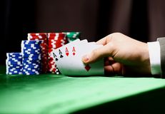 Poker. Chips and a hand flip the cards  against green felt Stock Image