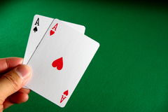 Pair of aces. A hand holding a pair of aces with a green table background Stock Photography