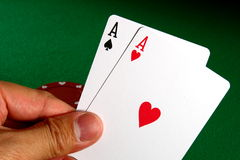 Poker Aces. Betting with the best Texas hold 'em poker starting hand of two aces, against green table background stock photo
