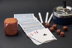 Poker of aces and wooden dice with a ashtray and cigarettes on a Royalty Free Stock Images