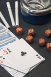 Poker of aces and wooden dice with a ashtray and cigarettes on a Royalty Free Stock Photography