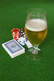 Poker and Beer. Poker table with chips beer dices and cards Royalty Free Stock Images