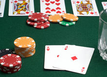 Poker cards and chips. Closeup of cards and chips in a poker game in progress, with the main focus on a pair of aces in the foreground stock photo