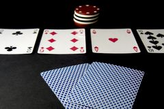 Poker cards and chips on black. Hands in focus, shallow royalty free stock photos