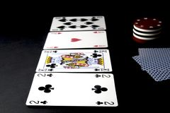 Poker cards and chips on black. River on the table with stock image