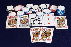 Poker cards Full House. Player shows his cards to reveal a full house and win lots of poker chips Stock Photo