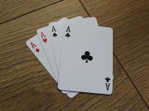 Poker cards on a wooden backround, set of ace of clubs, diamonds, spades, and hearts. Close up poker card ace set on wooden table Stock Photos