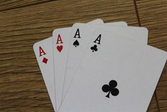 Poker cards on a wooden backround, set of ace of clubs, diamonds, spades, and hearts. Close up poker card ace set on wooden table Stock Images