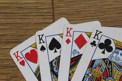 Poker cards on a wooden backround, set of kings of clubs, diamonds, spades, and hearts. Close up poker card kings set on wooden table Stock Photography