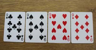 Poker cards on a wooden backround, set of nines of clubs, diamonds, spades, and hearts stock photos