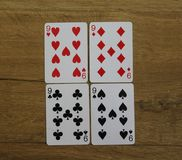 Poker cards on a wooden backround, set of nines of clubs, diamonds, spades, and hearts stock photo