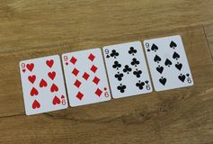Poker cards on a wooden backround, set of nines of clubs, diamonds, spades, and hearts stock image