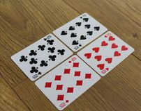 Poker cards on a wooden backround, set of tens of clubs, diamonds, spades, and hearts stock images